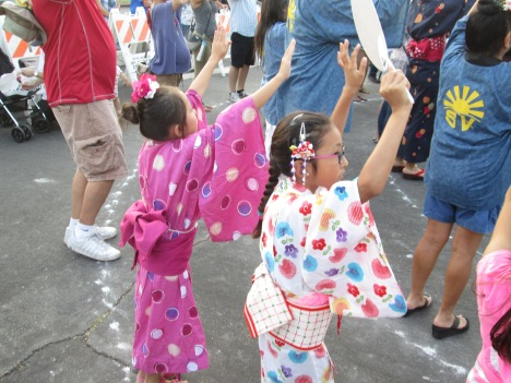 Two Little Girls in Kimonos Dancing to Honor Their Ancestors